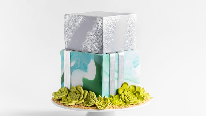 Learn how to make a smaller (but still awesome) version of James' Succulent Wedding Cake. Gold accents, gum paste succulents and eye-catching colors make this cake shine brighter than the rest.